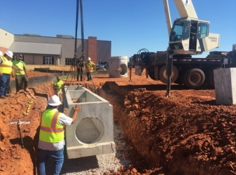 Installing large storm concrete box at construction site in Norman